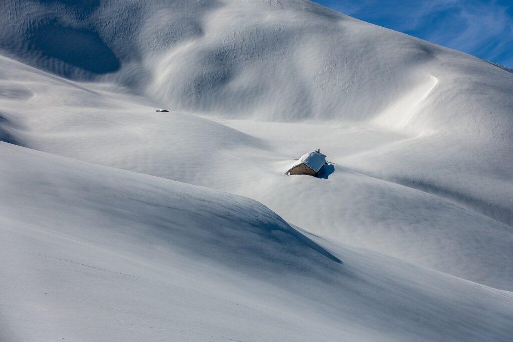 En ensam stuga omgiven och höljd av snö